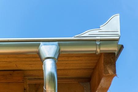 Nuevo drenaje galvanizado de agua de lluvia desde el techo. Agua para regar el jardín. Construyendo una casa ecológica