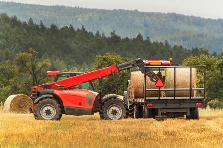 체코 공화국의 필드에 망원경 수집기 짚 수집. 농가에서 일하십시오. 짚 bales 수집 스톡 콘텐츠
