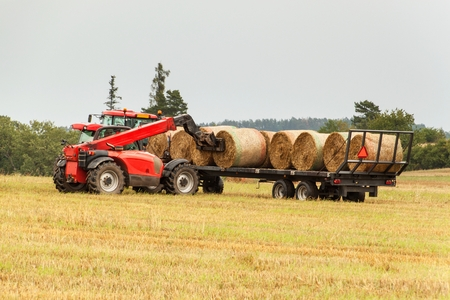 Telescopic collector straw collector on field in Czech Republic. Work on an agricultural farm. Collecting straw bales