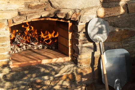 Home outdoor stone pizza oven. Traditional pizza production. Preparation of dinner