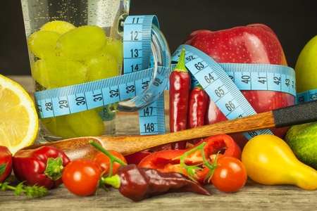 capsaicin: Glasses of water and a tailors meter. Fruits and vegetables. The concept of weight loss. Healthy diet