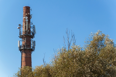 Telecommunication antennas on an old brick chimney. Industrial concept. Modern technology