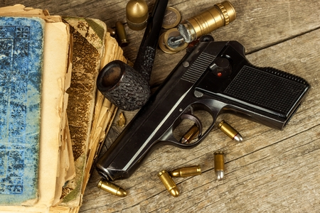 Gun and old book. Detective novel. Wooden tobacco pipe. Pistols and cartridges on the table
