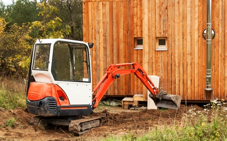 Work on the construction site of an ecological house. The excavator adjusts the terrain. A small digger in the garden Standard-Bild
