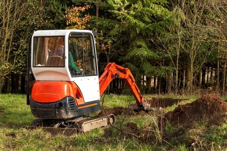 Trabajar en el sitio de construcción de una casa ecológica. La excavadora ajusta el terreno. Una pequeña excavadora en el jardín
