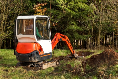 Work on the construction site of an ecological house. The excavator adjusts the terrain. A small digger in the garden Stockfoto