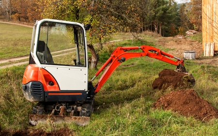 Mini excavator on site. Excavation work. The excavator works in the garden Stock Photo