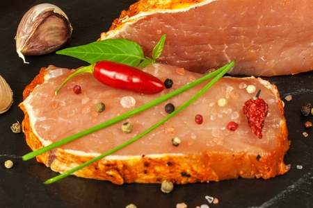 Raw pork chops with spices. Sliced ??meat prepared on the grill
