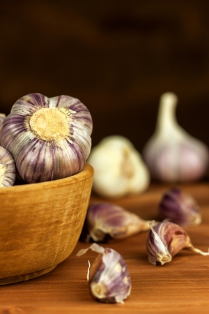 Garlic in a wooden bowl on a kitchen board. Superfood. Traditional folk medicine