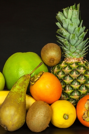 Different fruits on a black kitchen table. Food for athletes. Vitamins against colds and flu Stock Photo
