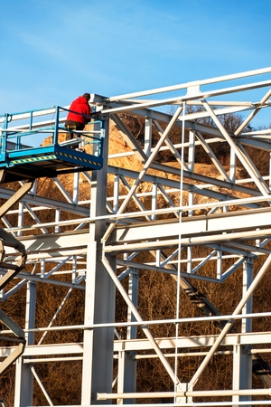The steel structure is under construction. Installation of metal halls. Work at height. A sunny day at a construction site. Stock Photo