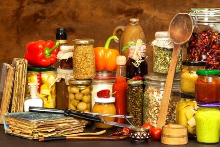Ingrediënten voor het koken op een houten tafel. Glas gekookte groenten en jam. Chef's werkplek