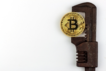 Bitcoin in the clamp. Risk of economic crisis. The fall of the currency. On a white background. Stock Photo