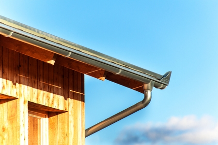 Rain gutter on the roof ecological house. Zinc gutter on the woodwork Stock Photo - 94755841