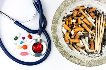 Cigarettes in a glass ashtray on a white background. Treatment of lung cancer.Stethoscope and medication Banque d'images