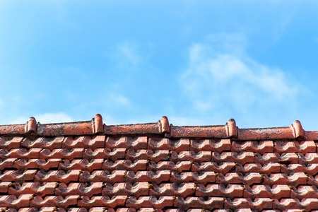 An old roof with burnt tiles. Roof in a village house against a blue sky background