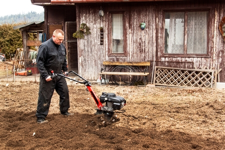 Farmer working in the field. Spring work on the farm. Man plowing the garden