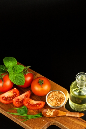 Tomatoes and herbs on a kitchen board. Preparation of healthy food. Raw vegetables. He and black background
