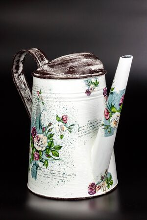 BRNO, CZECH REPUBLIC - 2 April, 2018: Products made by decoupage technique. Decoupage is a technique of decorating items of napkins. Metal ewer for watering