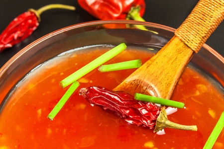 Sauce made of peppers. Preparation of spicy food. Healthy food. He and black background