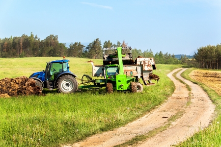 Natural manure agro bio fertilization. Loading manure onto tractor. Agricultural landscape in the Czech Republic