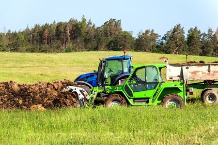 Natural manure agro bio fertilization. Loading manure onto tractor. Agricultural landscape in the Czech Republic