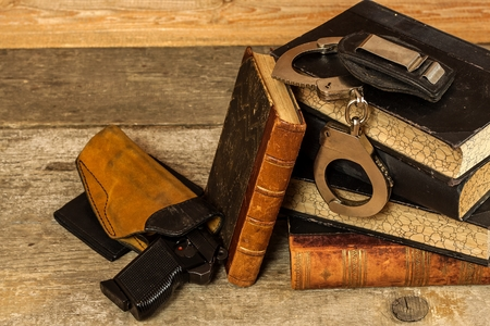 Police desk. Books of laws and police handcuffs. Investigation of crime. Gun and laws. Law and Order