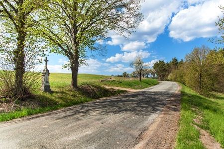 Catholic Cross at Country Road in the Czech Republic. Easter Monday. Old asphalt road.