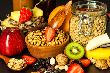 Healthy food background with homemade oatmeal granola or muesli with fruit. Muesli with nuts. Muesli on a black table. Food for athletes. Stock Photo