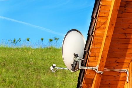 Antenne de télévision par satellite sur une maison en bois. Transmission du signal de télévision. Accès Internet. Moyens de télécommunication.