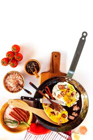 Fried egg with ham on a steel pan. Kitchen tools. Healthy breakfast. Vegetables and fried egg.