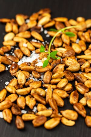 Roasted and salted sunflower seeds. Sunflower seeds in bowl over wooden background. Vegan food. Фото со стока