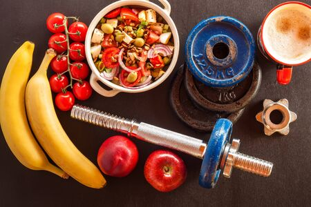 Vegetable salad and dumbbell. Weight reduction concept. Healthy food. Summer salad with tomato and pepper. Vegetarian food. Fruit.