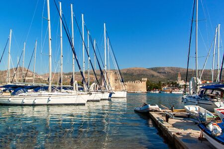 Summer morning in the harbor. Yachts parking in harbor, Harbor, Trogir, Croatia. Sailboats reflected in water. Boat rental. Stock Photo
