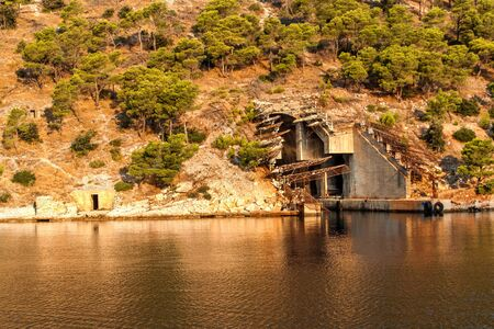 Submarine and ship bunker on Brac island, Croatia. Concrete bunker shelter for submarines in adriatic sea. Travel on a yacht in Croatia. Morning in the Bay of Smrka.