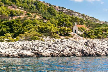 Church on the coast of Hvar island Croatia. View from the sea to the church in Malo Zarace. Rural church. Holiday in Croatia. View from sailboat. Banco de Imagens