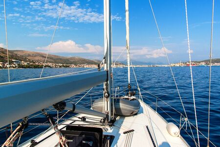 Sailboat sails to the port of Trogir in Croatia. View from deck of sailboat. Historic town on the Adriatic. Holiday in Croatia. Yachting sport. Stock Photo