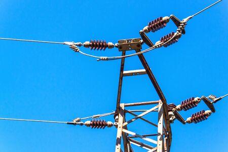 Distribution of electricity. Power pillar against blue sky. Ceramic insulator. Electrical energy.