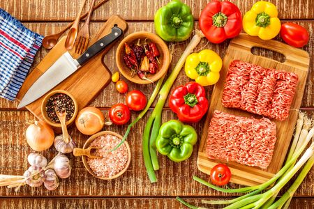 Raw minced meat. Preparation of stuffed peppers. Homemade food preparation. Vegetables and minced meat.