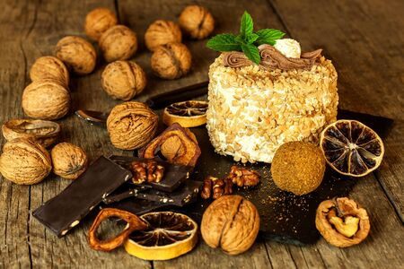 Sweet dessert. Walnut dessert. Tart on wooden table. Unhealthy food. Risk of diabetes. Walnuts.