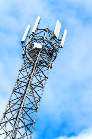 Telecommunication mast against blue sky. Autumn landscape with flagpole. Modern broadcast technology.