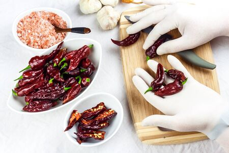 Male gloved hands sliced hot chilli pepper (Bhut Jolokia Chocolate). Preparation for drying. Sale of hot spices. Healthy spices. 스톡 콘텐츠