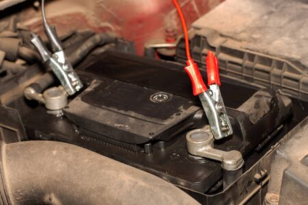 Charging an old car battery in a dirty engine. Preparing the car for winter season. Faulty car battery.