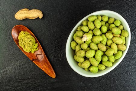 Wasabi Coated Peanuts on slate board. Japanese Wasabi Spice. Green wasabi peanuts on a black plate on a dark background.
