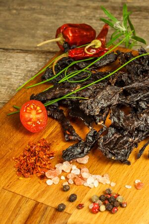 Dried meat on kitchen table. Domestic production of dried beef. Meat marinated in chilli. Diet food. Durable food. Proteins for athletes.