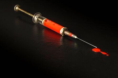 Syringe and blood on black background. Risk of HIV infection. Flu vaccination. Blood test. Old syringe