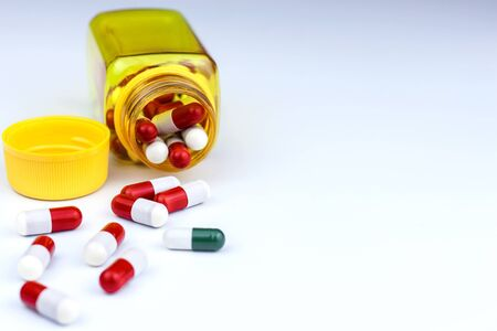 Red-white tablets on white background. Medicines in yellow jar. Pharmaceutical industry concept. Treatment of disease. Vitamin supplements. 写真素材