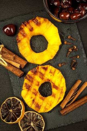 Grilled pineapple with pickled cherries. Homemade barbecue. Summer refreshment. Pineapple on the grill.