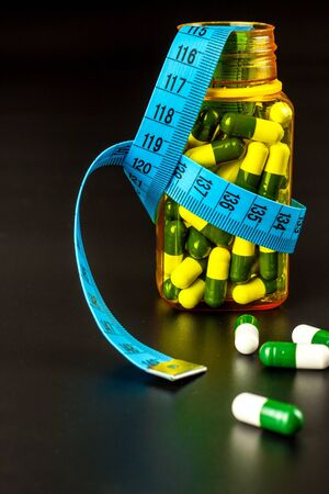 Pills with measuring tape. Weight loss concept. Obesity medications. Healthy life style. Dangerous obesity.