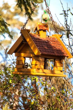 Garden Bird Feeder. Tree house for the birds, cheerful apartment. A self-made bird feeding house with a brown roof 写真素材